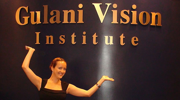 "A woman showcasing the sign ""Gulani Vision Institute"""